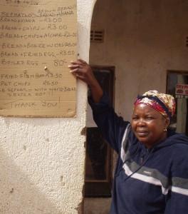 Microentreprenuer woman w/menu outside shop - S. Africa